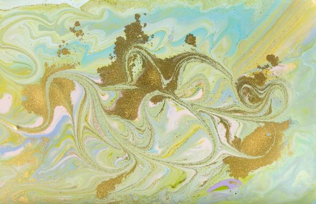 緑と金を注ぐ絵画。淡い美しい背景。