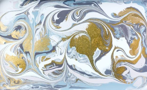 金色キラキラと青と紫の絵。液体の抽象的な背景。