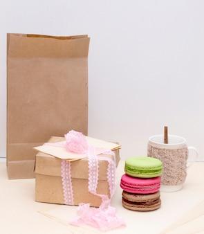 Вязаная кружка и разноцветные миндальные печенья на грубом бумажном пакете