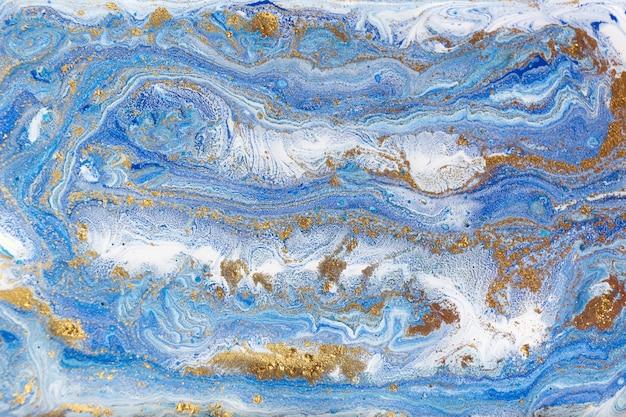 ブルーとゴールドの霜降り。黄金の大理石の液体テクスチャ。