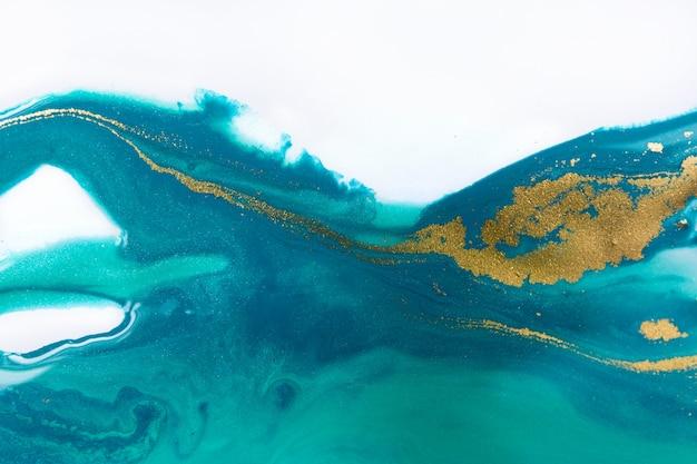 ゴールドのスパンコールの層がある青い液体の波。