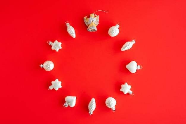 Круглая рамка композиция с елкой из белого стекла игрушки на красной бумаге. рождество