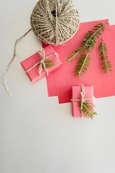 Рождество с подарочные коробки, клубки веревки, бумаги и украшения на красный. подарочная упаковка . вид сверху.
