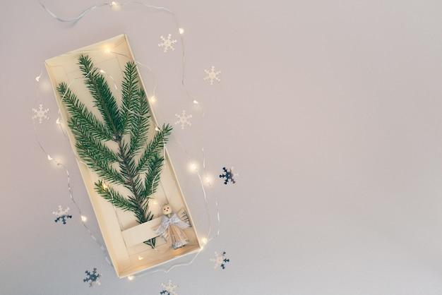 Минималистичная новогодняя елка из вечнозеленого елового растения, украшенная ангелом и светящейся гирляндой на белой бумаге.