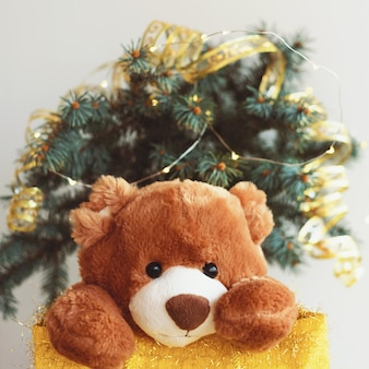 Рождественская открытка с мишкой на подарочной сумке.
