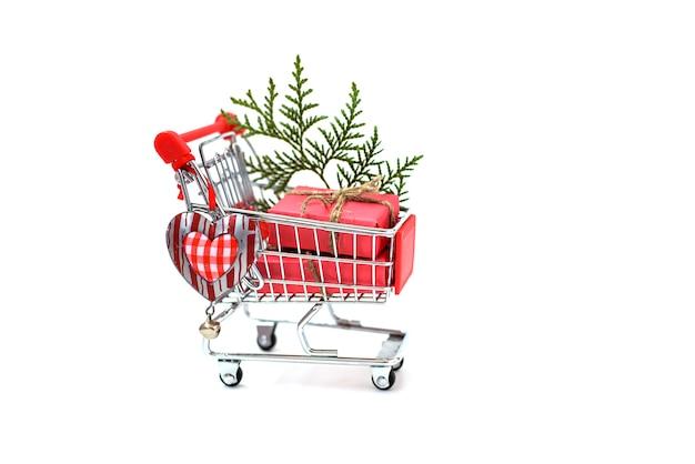 Рождественские подарки в тележке супермаркета на белом