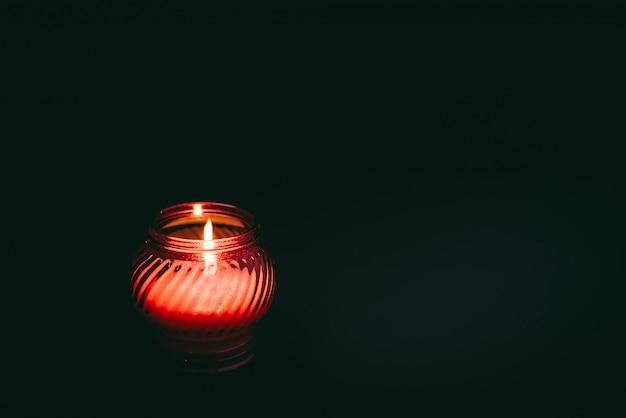 Белая горящая свеча в красном стекле на черной предпосылке. траур, грусть, печаль.