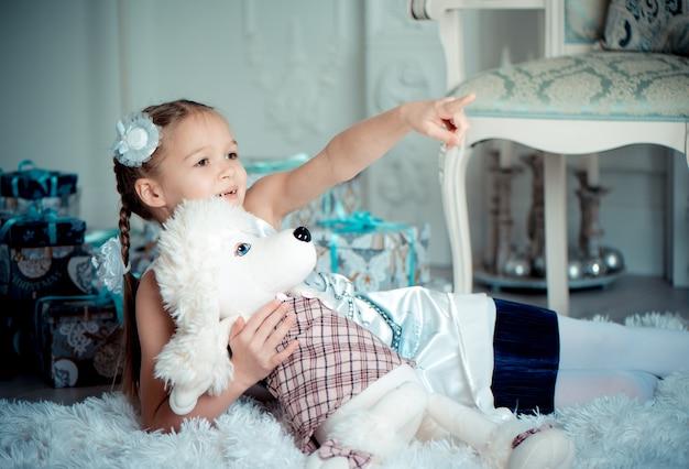 誕生日のおもちゃプレゼントで遊ぶ愛らしいエレガントな少女。彼女はおもちゃでカーペットの上に横たわり、何かを指で指します。