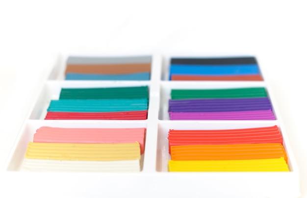 Открытая коробка с новым набором разноцветного пластилина.