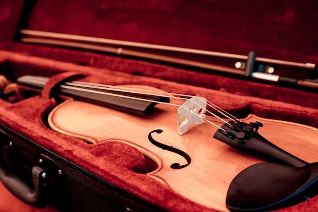 バイオリンとダークレッドのケースの弓。バイオリンのクローズアップ表示