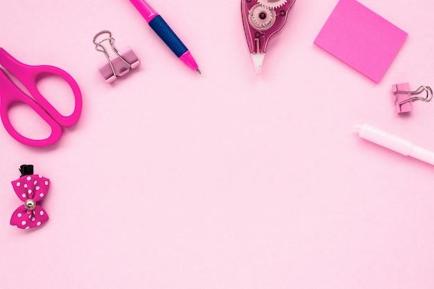 ピンクの背景の学校の文房具。学校のコンセプトに戻る