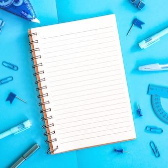 青いパステルカラーの学用品学校のコンセプトに戻るフラットレイアウトトップビュー