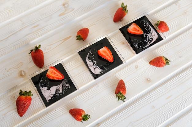 白い背景の上に、新鮮なイチゴとガラスのカスタードデザート