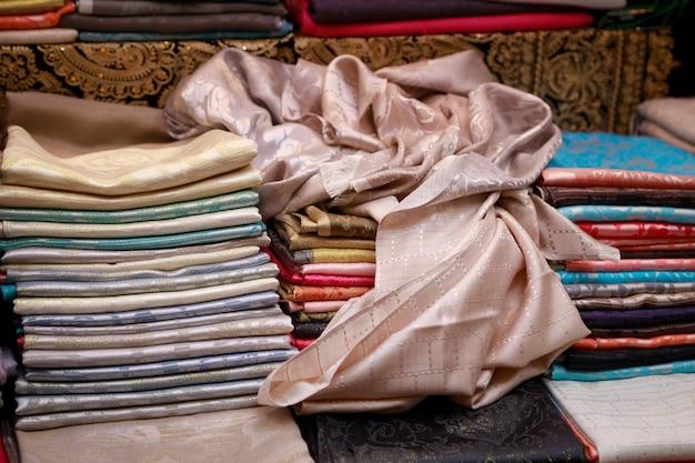 На прилавке лежат тонкие красивые платки пашмины ручной работы