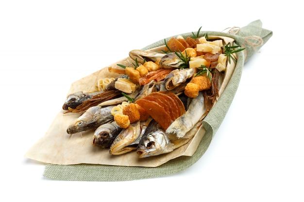 さまざまな品種の塩干しストックフィッシュ、乾燥イカのスライス、および他の魚からなる花束は、白い表面にあります。閉じる
