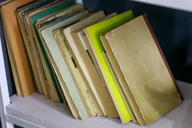 Много разных книг на открытой полке у стены