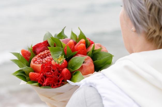 女性は彼女の手でリンゴ、ザクロ、イチゴ、花の美しい花束を保持しています。