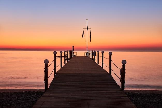 暖かく穏やかな海と木製のポンツーンの夜明けの景色
