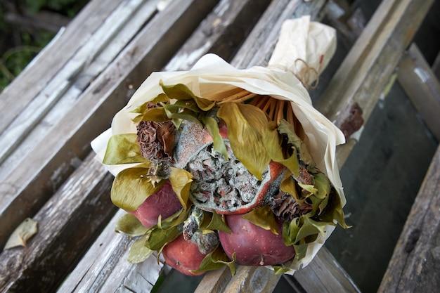 壊れた木造家屋の遺跡にある腐った果物としおれた花の花束