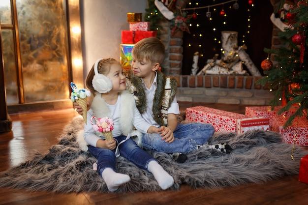 幸せな子供たちはクリスマスツリーの近くの床に座って、甘い贈り物を食べる