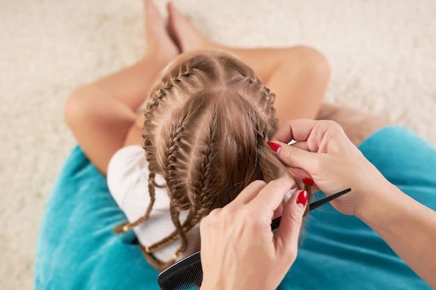 ママは娘のおさげ髪を編む