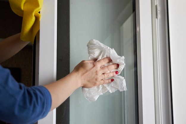 女性はペーパータオルを使用してウィンドウを拭く
