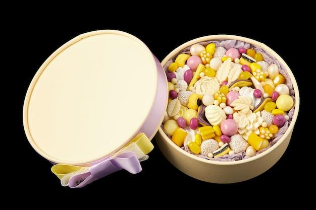 黒に分離された手作りのチョコレート菓子で満たされた黄色の丸い箱