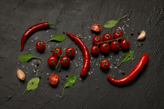 Стручки острого перца чили, помидоры черри, чеснок, листья руколы и специи на черном