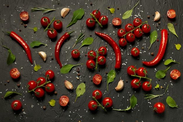 Множество помидоров черри, стручки острого перца, листья рукколы и салата, чеснок и специи лежат на черном