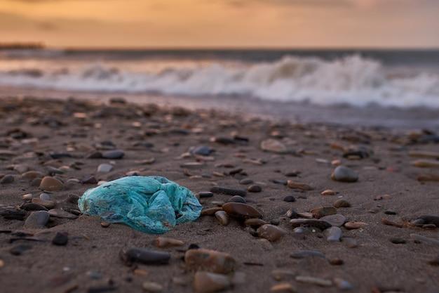 ビーチに横たわっているビニール袋の形のゴミ