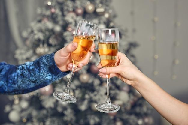 男性と女性の手がグラスシャンパンを保持します。