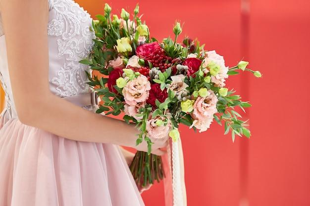 ピンクのドレスを着た花嫁は、カーネーションとバラの美しい花束を持って立っています。