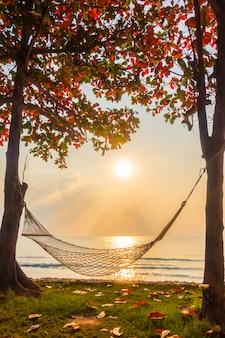 日の出時間にビーチと海に近いハンモック