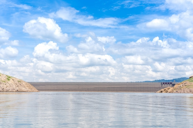 Ландшафт озера и бетонной плотины во время солнечного дня.