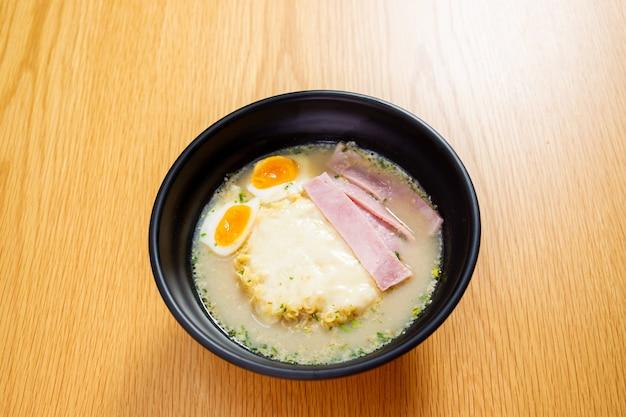 木製のテーブルのハムチーズとゆで卵麺をクローズアップ。