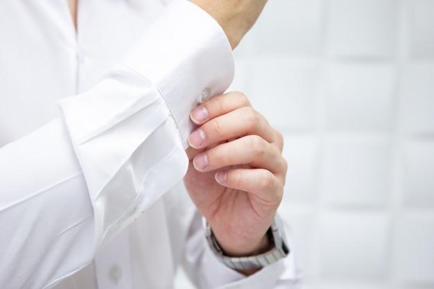 彼のシャツを調整するビジネスの男性をクローズアップ。