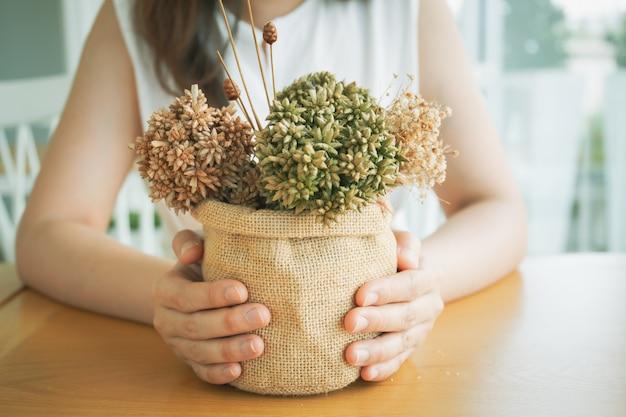 彼女のビンテージコーヒーバーで花の花束を飾る美しい少女をクローズアップ。