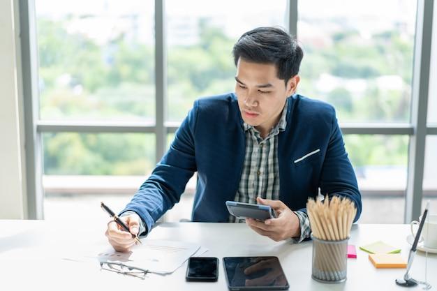 オフィスで働くスマートハンサムなアジア系のビジネスマンをクローズアップ。現代の職場と現代のライフスタイル。
