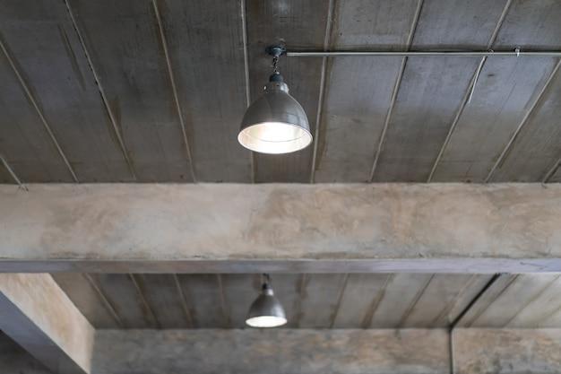 Потолочная лампа в здании, которое оформлено в стиле лофт и индустриального стиля крупным планом.