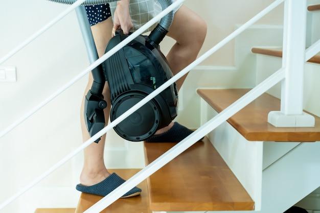 アジアの家政婦が階段の上に立って、真空を運ぶをクローズアップ。