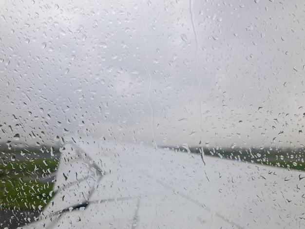 飛行機の窓の外に雨が降る