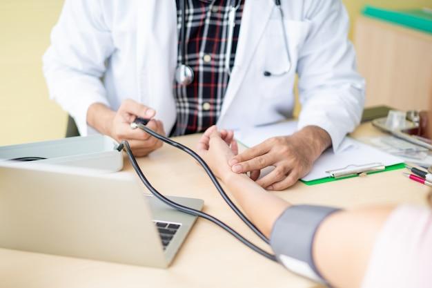 Доктор проверяя его терпеливое кровяное давление. концепция здорового ухода и хорошего самочувствия.