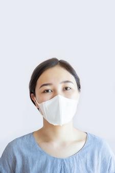 Портрет азиатской милой женщины нося конец лицевой маски гигиены вверх.
