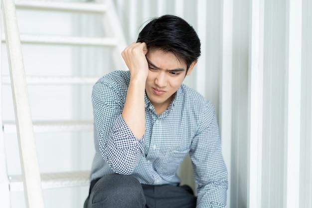 階段の上に座って絶望的なアジア系のビジネスマン。アジア系のビジネスマンの肖像画を強調