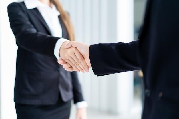 ビジネスマンやビジネスウーマンのビジネストークの後に握手をしています。プロのビジネス人々の概念。