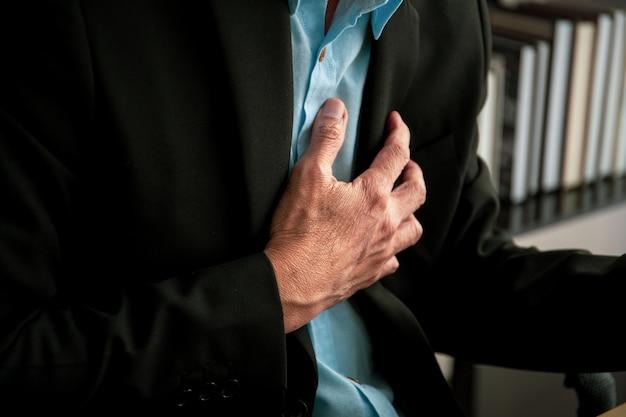 アジアの老人ビジネスマンは健康上の問題を抱え、アジアの仕事中毒のビジネスマンに心臓発作を起こしました。