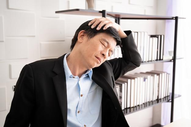 У азиатского старшего делового человека есть проблема офисного синдрома от трудолюбия. здравоохранение и работа концепции баланса жизни в трудящихся.