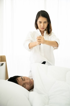 妻がナイフを持って、ベッドで寝ている夫を狙っています。家族の問題と離婚の概念。