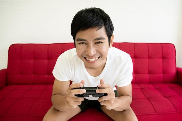 アジアの若い男が赤いソファに座って、ビデオゲームをプレイすることに集中します。男はビデオゲームをプレイ中毒。
