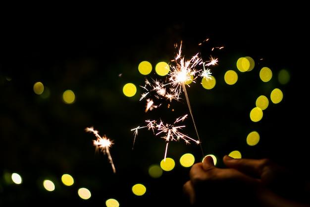 女の子は小さな線香花火手花火で遊んで、クリスマスと新年の祭りで祝います。